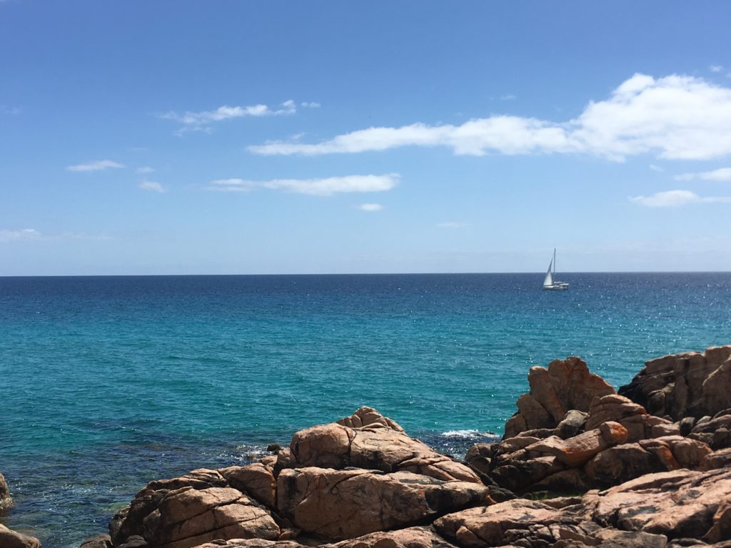 boat sailing on the ocean with rocks in foreground.